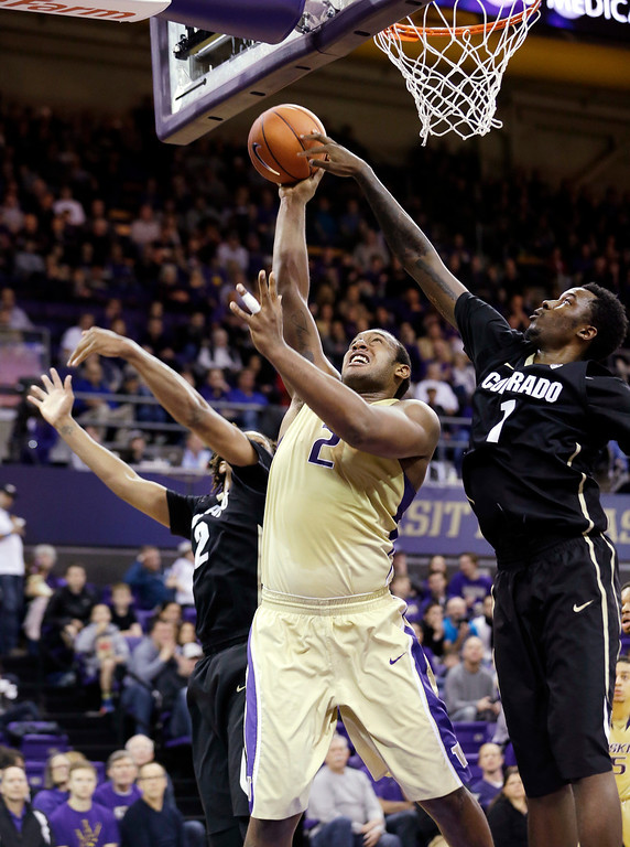 . Washington\'s Perris Blackwell, center, puts up a shot between Colorado\'s Xavier Johnson, left, and Wesley Gordon in the first half of an NCAA college basketball game, Sunday, Jan. 12, 2014, in Seattle. Washington won 71-54. (AP Photo/Elaine Thompson)