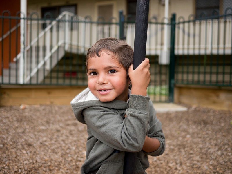 This photo shows a five-year-old Aboriginal boy in an urban setting in the Greater City of Melbourne, Australia.  The photo was made in the playground of a housing estate.  He is holding onto a pice of playground equipment.