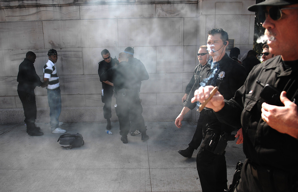 . A Denver police officer smoke a cigar as he and other officers patrol the crowds as thousands of pot-smokers gathered for the annual 420 smoke out  at Civic Center Park in down town Denver. Officers arrest a few of the goers. RJ Sangosti / The Denver Post.