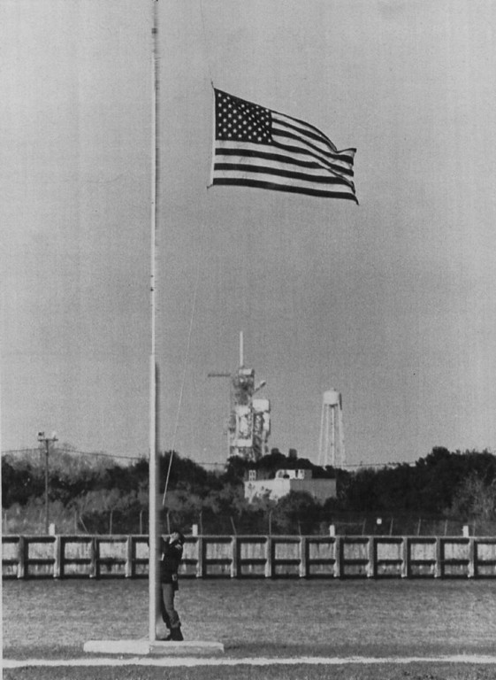. A Kennedy Space Center security guard lowers the flag to half mast at the press center on Jan. 28, 1986 in memory of the seven astronauts that perished aboard space shuttle Challenger. Launch pad 39B where the orbiter lifted off can be seen in the background.  Denver Post Library Archive