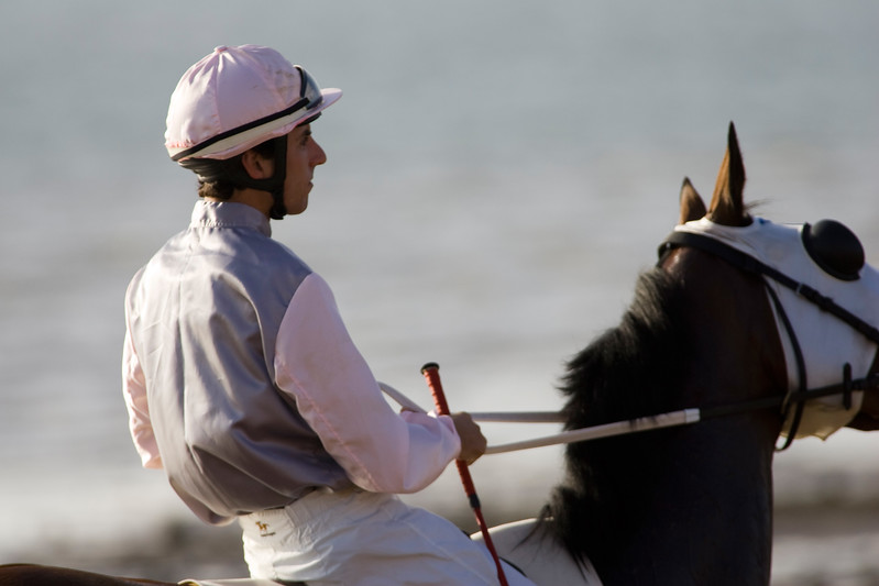 "Thoroughbred horses compete at sea shore with green horizon of ""Doñana National Park"" and the whole seafront in Sanlucar de Barrameda, Cadiz, Spain. The races date back to the 19th century."