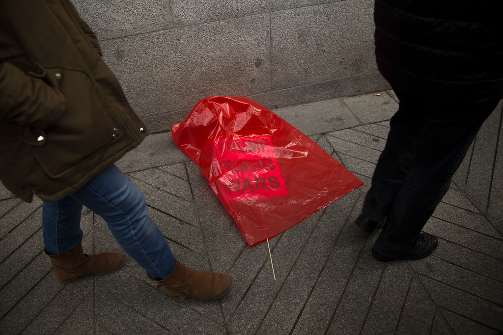 . People walk past a small placard left inside a plastic bag during an anti-Trump protest outside the US embassy in Madrid, Saturday, Jan. 21, 2017. Donald Trump took the oath of office as the 45th President of the United States on Friday. (AP Photo/Francisco Seco)