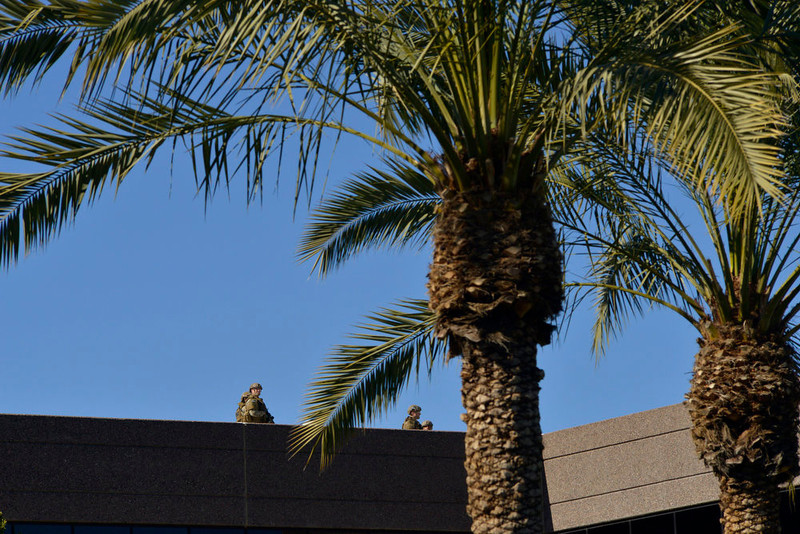 . SWAT police officers inspect the roof of an office building after a shooting at the building in Phoenix on Wednesday, Jan. 30, 2013. A gunman opened fire at the Phoenix office building, wounding three people, one of them critically, authorities said. Police were searching for the shooter. (AP Photo/Patrick Sison)