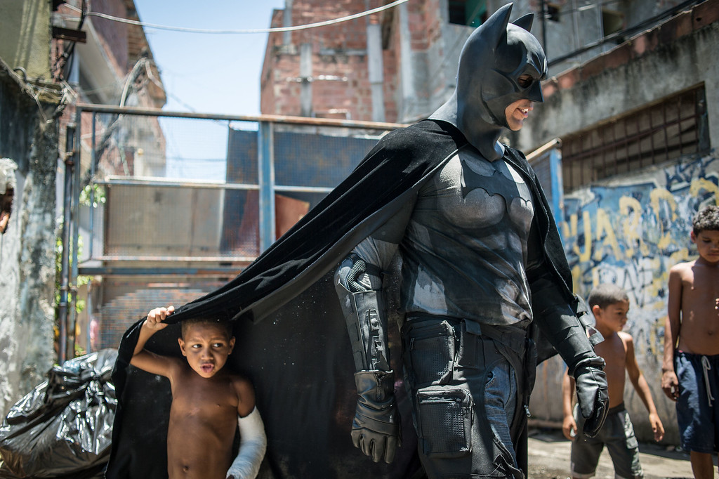 . Children play around a man disguised as Batman at the Favela do Metro slum, area just near the Maracana stadium, in Rio de Janeiro, Brazil, on January 9, 2014. Families living in this shantytown within a stone\'s throw of Rio\'s mythical Maracana stadium refuse to have their homes demolished as part of a project to renovate the district before the FIFA World Cup circus pitches camp in June.  AFP PHOTO / YASUYOSHI CHIBA/AFP/Getty Images