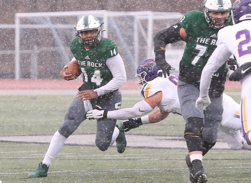 Slippery Rock quarterback Roland Rivers III eludes a would-be tackle during Saturday's playoff game against Minnesota State. Defensive pressure all game caused the offense to struggle in the 58-8 loss. Seb Foltz/Butler Eagle