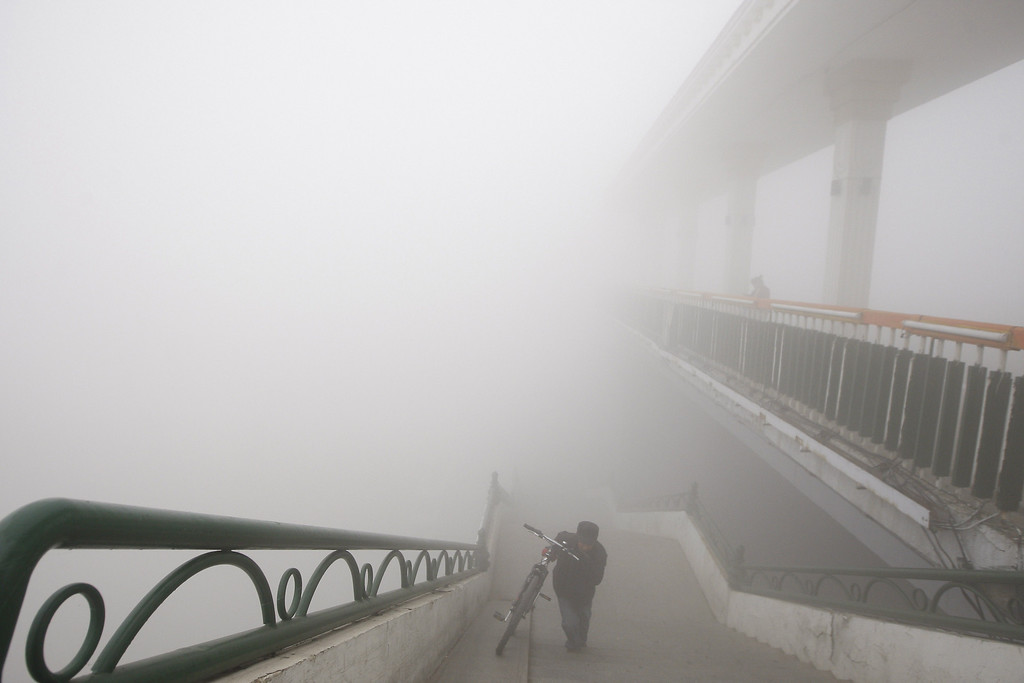 . A man pushes his bike onto a bridge under heavy smog in Harbin, northeast China\'s Heilongjiang province, on October 21, 2013.  AFP PHOTOSTR/AFP/Getty Images