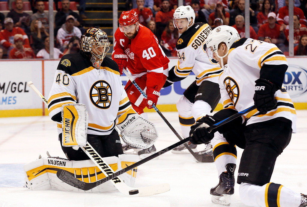 . Boston Bruins goalie Tuukka Rask (40) stops a shot as defenseman Dougie Hamilton (27) and Carl Soderberg (34) also defend against Detroit Red Wings left wing Henrik Zetterberg (40), of Sweden, in the second period of an NHL hockey game in Detroit, Thursday, Oct. 9, 2014. (AP Photo/Paul Sancya)