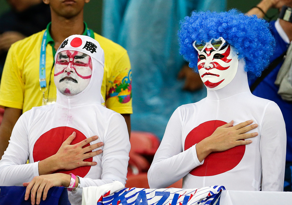 . Japanese fans listen to their nation\'s national anthem before the group C World Cup soccer match between Ivory Coast and Japan at the Arena Pernambuco in Recife, Brazil, Saturday, June 14, 2014. (AP Photo/Petr David Josek)
