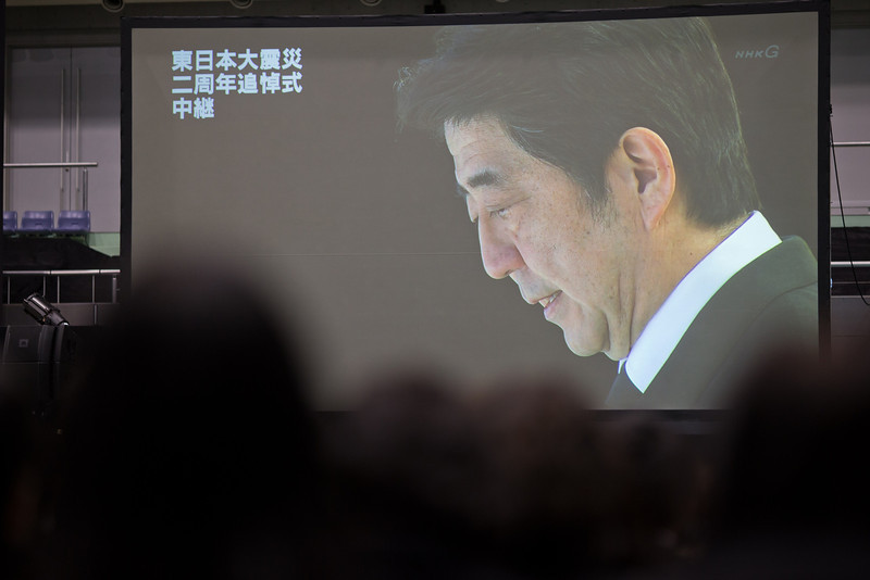 . People watch Prime Minister Shinzo Abe projected on a large screen during a memorial ceremony to commemorate the victims of the 2011 earthquake and subsequent tsunami on March 11, 2013 in Kesennuma, Japan. Japan is commemorating the second anniversary of the 2011 Magnitude 9.0 earthquake and subsequent tsunami that claimed more than 18,000 lives.  (Photo by Athit Perawongmetha/Getty Images)