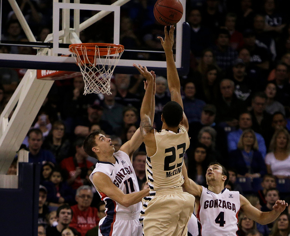 . Oakland\'s Tommy McCune (23) attempts a jump shot against Gonzaga�s David Stockton (11) and Kevin Pangos (4) during the first half of an NCAA basketball game, in Spokane, Wash., on Sunday, Nov. 17, 2013. (AP Photo/Young Kwak)