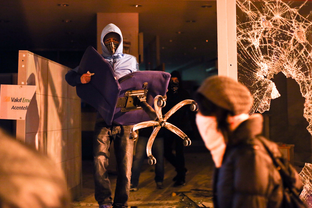 . A protester carries a chair out of a bank during clashes between police and demonstrators after the funeral of Berkin Elvan, the 15-year-old boy who died from injuries suffered during last year\'s anti-government protests, in Istanbul on March 12, 2014. Riot police fired tear gas and water cannon at protesters in Ankara and Istanbulas tens of thousands took to the streets to mourn a teenage boy who died from injuries suffered in last year\'s anti-government protests. Elvan\'s story became a symbol for many Turks of the heavy-handed police tactics against mass anti-government demonstrators in June, a major challenge to Erdogan\'s 11-year-rule. (GURCAN OZTURK/AFP/Getty Images)