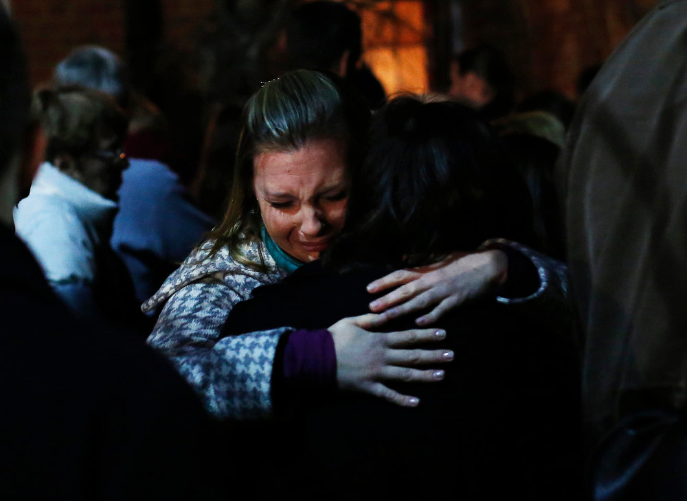 . People grieve outside the overflow area of a vigil at the Saint Rose of Lima church in Newtown, Connecticut December 14, 2012. A heavily armed gunman opened fire on school children and staff at a Connecticut elementary school on Friday, killing at least 26 people, including 20 children, in the latest in a series of shooting rampages that have tormented the United States this year.  REUTERS/Shannon Stapleton