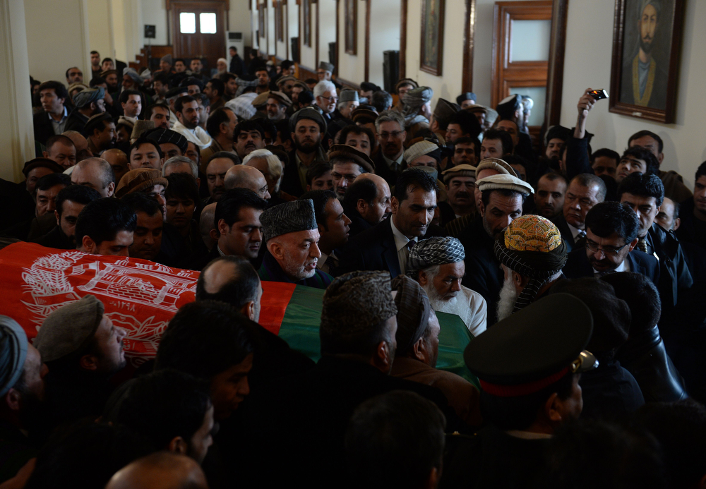 . Afghan President Hamid Karzai (C) with others carries the flag-covered coffin of Afghan Vice-President Marshal Mohammad Qasim Fahim, formerly one of the country\'s most feared warlords during his burial ceremony at the Presidential Palace in Kabul on March 11, 2014. Afghan Vice-President Marshal Mohammad Qasim Fahim, formerly one of the country\'s most feared warlords, died of natural causes after a turbulent life that reflected the country\'s recent past. Fahim, a leader of the Tajik ethnic minority, was senior vice-president under President Hamid Karzai, who will step down at elections next month as US-led combat forces pull out of Afghanistan after 13 years of fighting the Taliban. (SHAH MARAI/AFP/Getty Images)