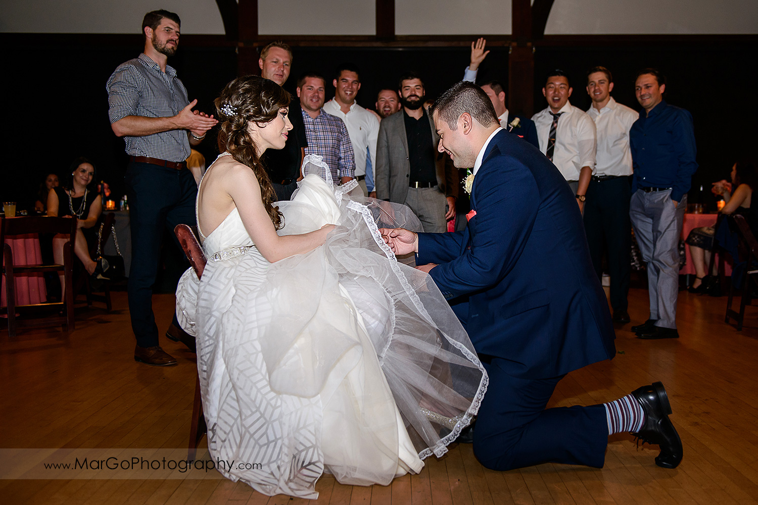 groom removing bride's garter during wedding reception at Saratoga Foothill Club