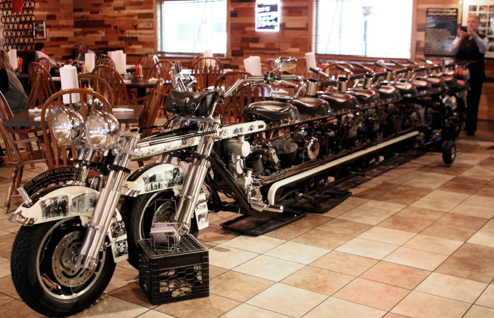 ". In this Oct. 22, 2012 photo, a restaurant patron at the Timeline Restaurant in Bonduel, Wis. takes a photo of Doc\'s Harley-Davidson\'s 10-seat Timeline Motorcycle that owner Steve ""Doc\"" Hopkins built in 2009. The motorcycle left this week for an auto show in Essen, Germany. (AP Photo/Shawano Leader, Cory Dellenbach)"