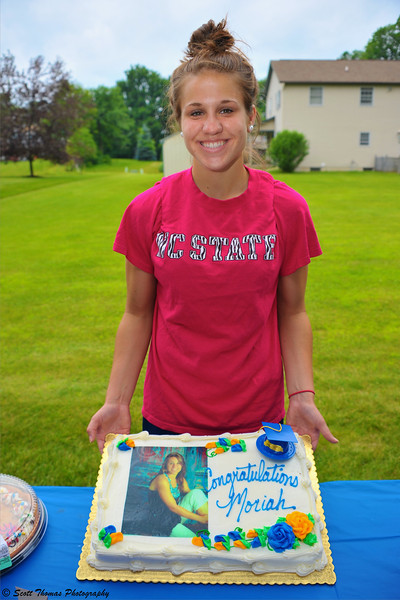 A 2011 high school graduate poses with her cake at her graduation party.
