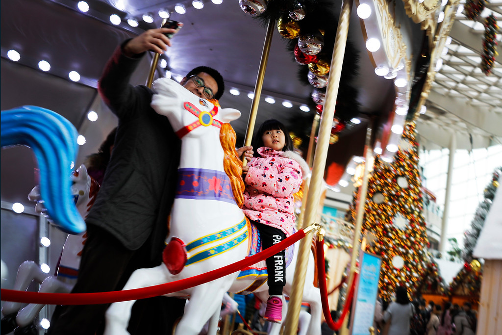 . A man and his daughter pose for a selfie while riding on a carousel at a shopping mall with Christmas decorations in Beijing, Sunday, Dec. 25, 2016. Although Christmas is not traditionally celebrated in China, shopping malls and retailers welcome the festival by organizing activities to attract shoppers as a chance to boost year-end sales. (AP Photo/Andy Wong)