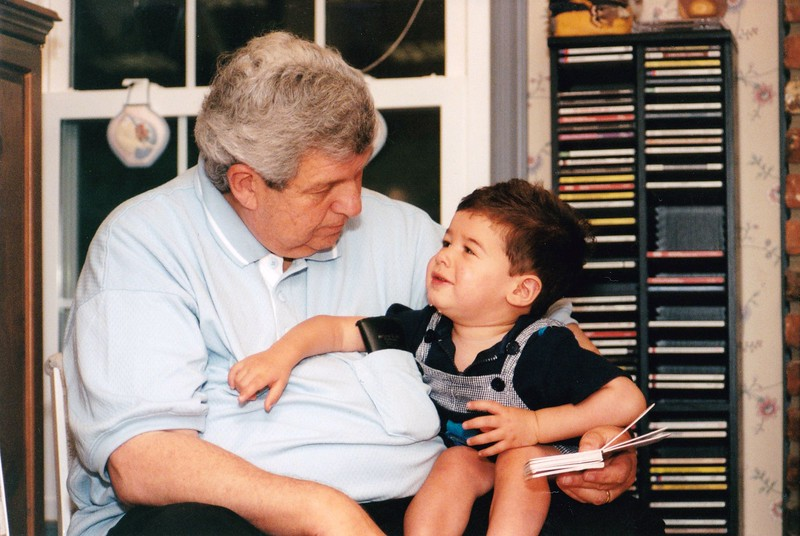 1999-06#21  Josh with Grandpa Gerry and board book in front of CD rack.jpg