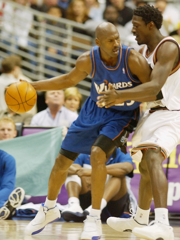 . Washington Wizards guard Michael Jordan, left, works the ball inside for a shot against Denver Nuggets forward Donnell Harvey in the first quarter in Denver on Sunday, March 30, 2003. (AP Photo/David Zalubowski)