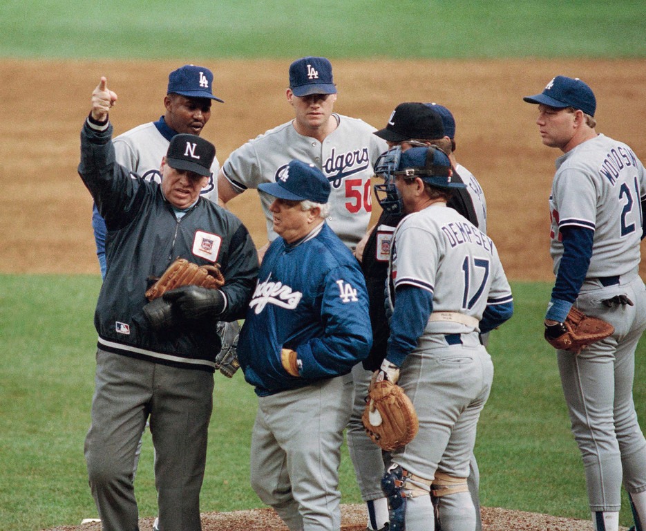 . Umpire crew chief Harry Wendelstedt, left, signals the ejection of Los Angeles Dodgers pitcher Jay Howell, right rear, after a possible illegal substance was found in Howell\'s glove in the eighth inning of playoff game, Saturday, Oct. 8, 1988, New York. Dodger manager Tom Lasorda, center, talks to Wendelstedt. The rest of the players are unidentified. (AP Photo/Bill Kostroun)