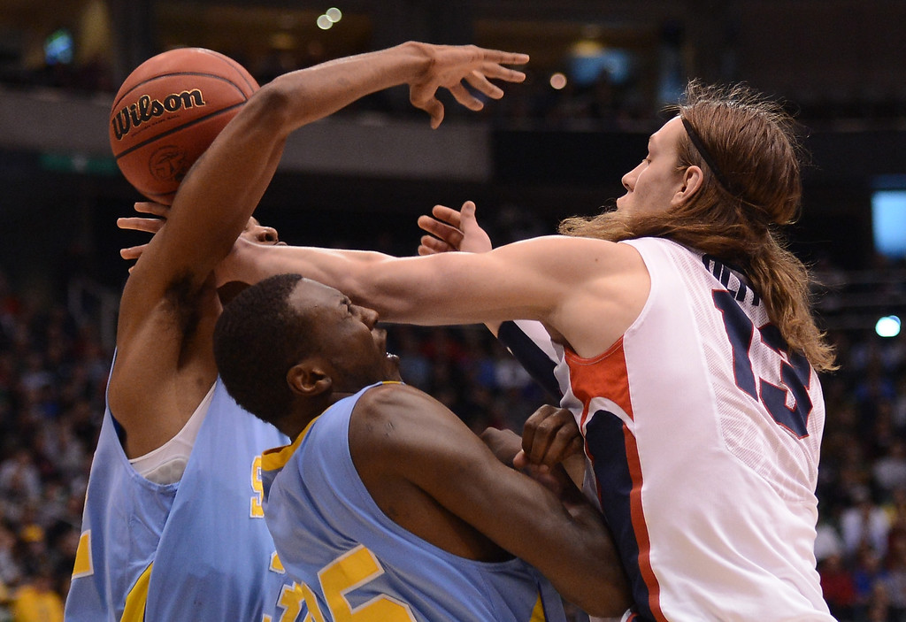 . SALT LAKE CITY, UT - MARCH 21:  Kelly Olynyk #13 of the Gonzaga Bulldogs goes for the ball against Madut Bol #35 and Brandon Moore #32 of the Southern University Jaguars in the first half during the second round of the 2013 NCAA Men\'s Basketball Tournament at EnergySolutions Arena on March 21, 2013 in Salt Lake City, Utah.  (Photo by Harry How/Getty Images)