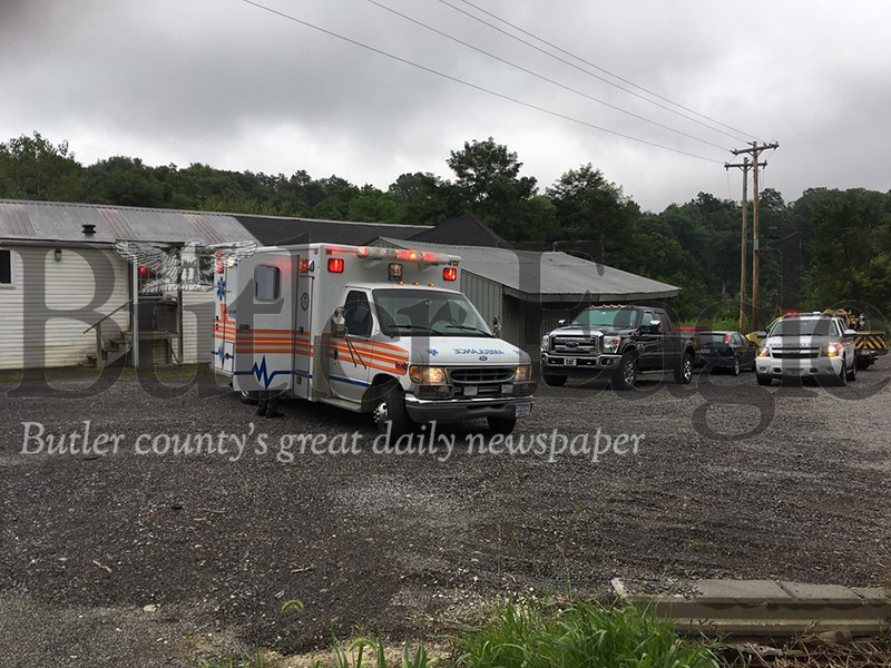 A Butler Ambulance Service crew waits to take an employee injured in an on-the-job accident Wednesday morning at Semper Concrete in Franklin Township. The worker's right hand was severed while he used a mixer.