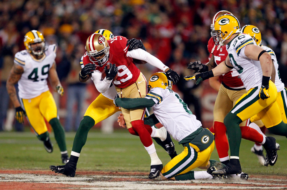 . San Francisco 49ers wide receiver Ted Ginn Jr. (19) is tackled by Green Bay Packers linebacker Terrell Manning, rear, and punter Tim Masthay (8) during the first quarter of an NFC divisional playoff NFL football game in San Francisco, Saturday, Jan. 12, 2013. (AP Photo/Tony Avelar)