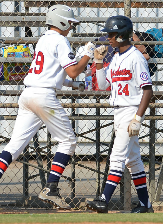 . Westchester\'s Nick Goff (24) bumps fists with Matthew Kanfer as they begin the scoring in the first inning against Torrance in a Babe Ruth final at Kendall Park in Torrance Thursday. Westchester won the first game 6-5.