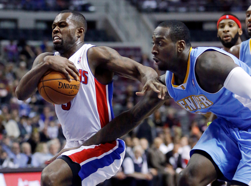 . Detroit Pistons guard Rodney Stuckey, left, drives to the basket past Denver Nuggets center JJ Hickson during the second half of an NBA basketball game on Saturday, Feb. 8, 2014, in Auburn Hills, Mich. The Pistons won 126-109. (AP Photo/Duane Burleson)
