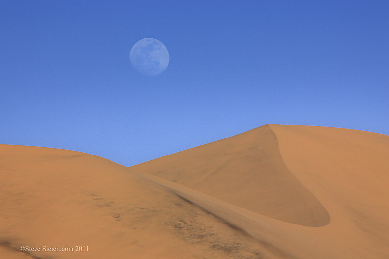The full moon rising over the Eureka Dunes in the Northern part of Death Valley National Park.