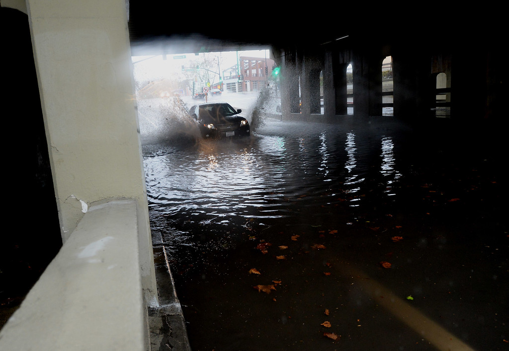 . Car car drives through standing water under the CalTrain over pass along Santa Clara St. in San Jose, Calif., on Thursday, Dec. 11, 2014. The big storm made its way south, after pounding the North Bay in the early morning hours. Flooding caused the eventual closing of the street. (Dan Honda/Bay Area News Group)