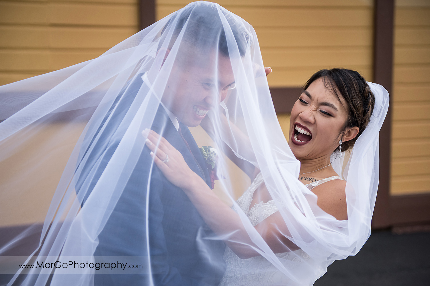 bride and groom haaving fun under the veil at train station near Sunol's Casa Bella