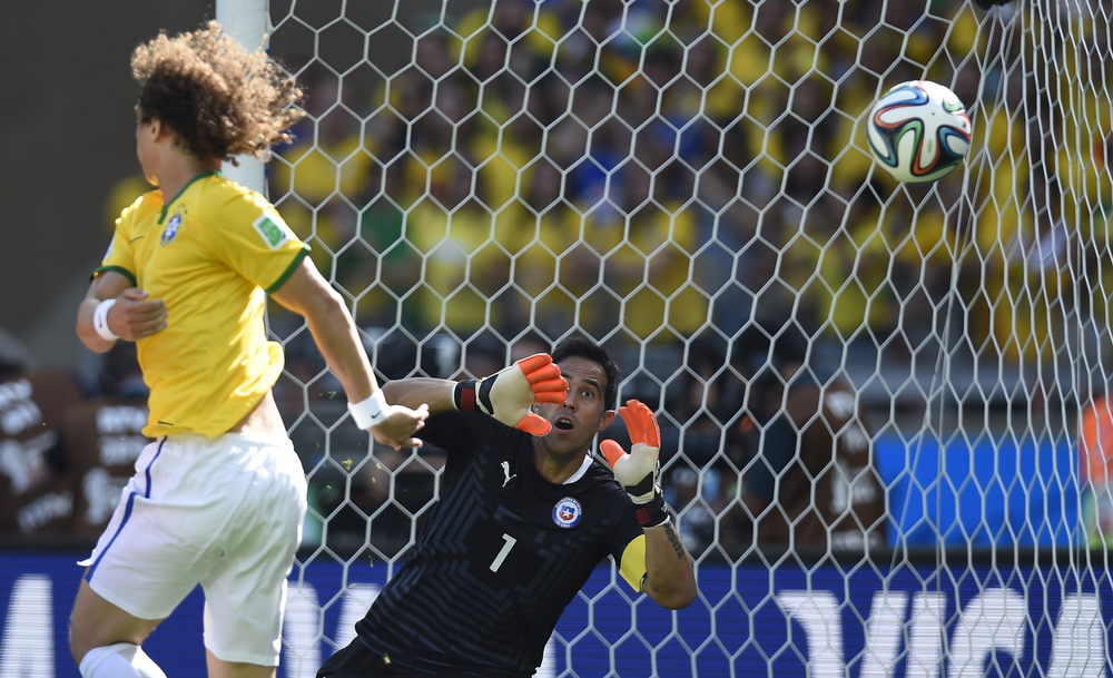 . Chile\'s goalkeeper Claudio Bravo (R) concedes a goal to Brazil during the round of 16 football match between Brazil and Chile at The Mineirao Stadium in Belo Horizonte during the 2014 FIFA World Cup on June 28, 2014. (FABRICE COFFRINI/AFP/Getty Images)