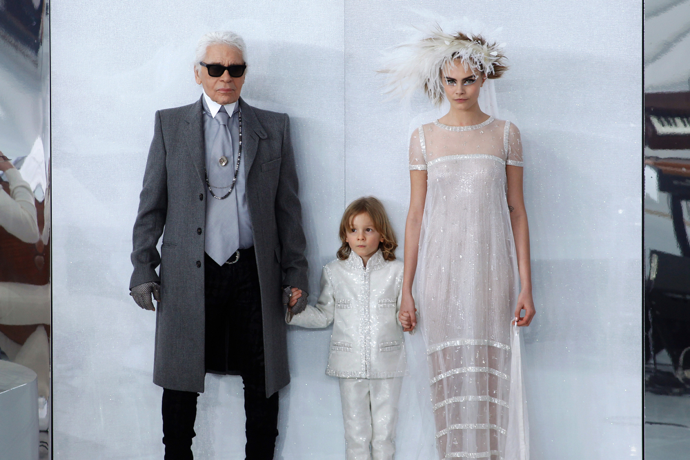 . From left, German fashion designer Karl Lagerfeld, Hudson Kroenig, son of US model Brad Kroening, and model Cara Delevingne pose at the end of the Chanel Spring-Summer 2014 Haute Couture fashion collection, presented Tuesday, Jan. 21, 2014 in Paris. (AP Photo/Thibault Camus)
