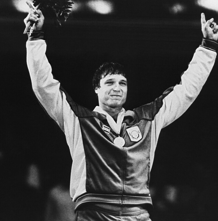 . FILE - This Aug. 3, 1984 file photo shows Greco-Roman wrestling gold medalist Jeff Blatnick gesturing during ceremonies at the Summer Olympics in Los Angeles.  Blatnick, who overcame cancer to win a gold medal in Greco-Roman wrestling at the 1984 Summer Olympics, has died in New York state at age 55.  Ellis Hospital in Schenectady, N.Y., said Wednesday Oct. 24, 2012, that he died there of heart failure.(AP Photo/Doug Pizac, File)