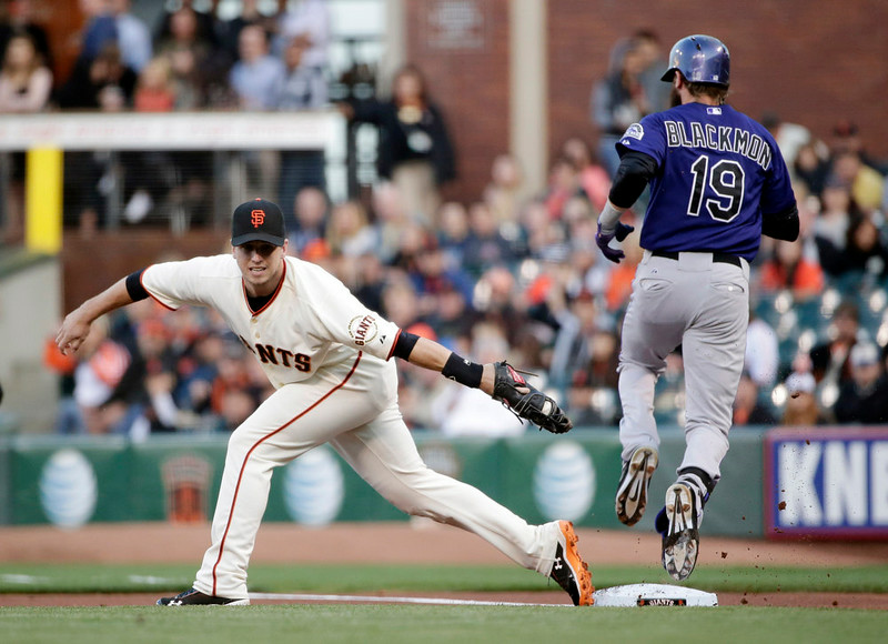 . San Francisco Giants first baseman Buster Posey, left, comes off the base while catching an errant throw from second baseman Joe Panik, allowing Colorado Rockies\' Charlie Blackmon (19) to reach first base safely during the first inning of a baseball game Monday, Aug. 25, 2014, in San Francisco. (AP Photo/Marcio Jose Sanchez)