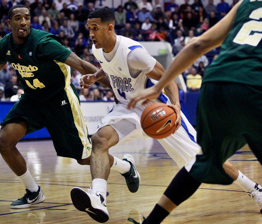 . Air Force\'s Kamryn Williams, center, moves the ball downcourt while covered by Colorado State\'s Greg Smith, left, during the second half of an NCAA college basketball game in Air Force Academy, Colo., Saturday, Feb. 16, 2013. Colorado State won 89-86. (AP Photo/Brennan Linsley)