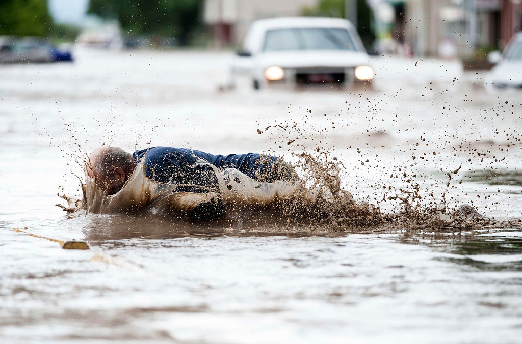 . Francois Gougeon trips and falls into floodwater while checking on his downtown store on High River\'s main street in Alberta province June 20, 2013. Gougeon was wet but otherwise uninjured. A state of emergency has been issued for the town of High River, which is being evacuated due to floods. REUTERS/Mike Sturk