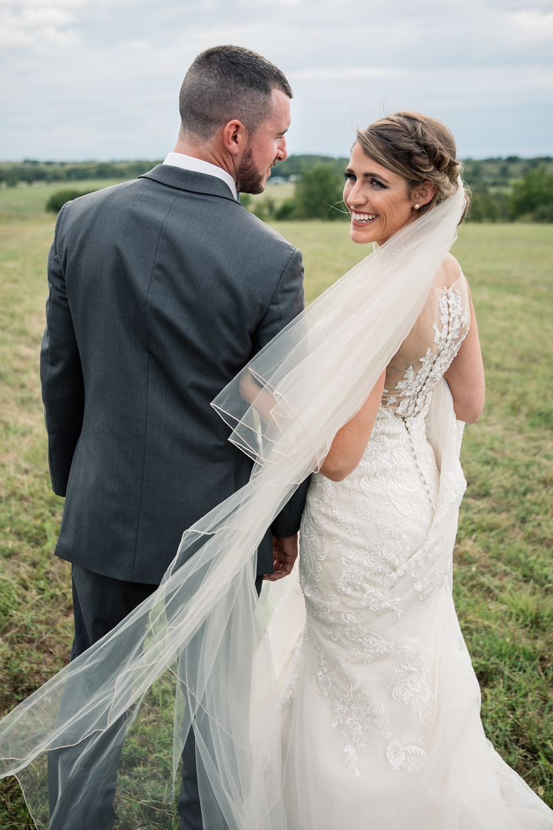 a bride looking back over her shoulder while holding her grooms arm as they walk through a field before their wedding
