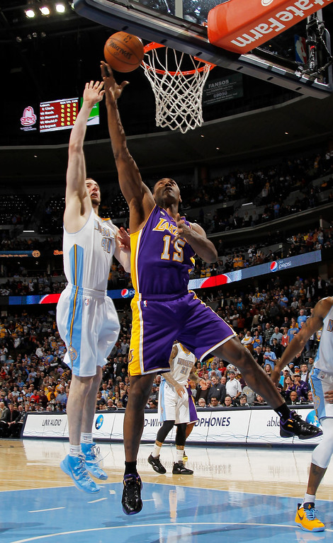 . Los Angeles Lakers forward Metta World Peace, right, goes up for a shot as Denver Nuggets center Kosta Koufos defends in the first quarter of an NBA basketball game in Denver on Monday, Feb. 25, 2013. (AP Photo/David Zalubowski)