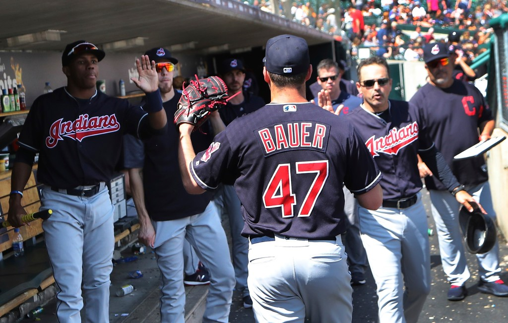 . Cleveland Indians starting pitcher Trevor Bauer is greeted in the dugout after completing the eighth inning of a baseball game against the Detroit Tigers, Wednesday, May 16, 2018, in Detroit. (AP Photo/Carlos Osorio)
