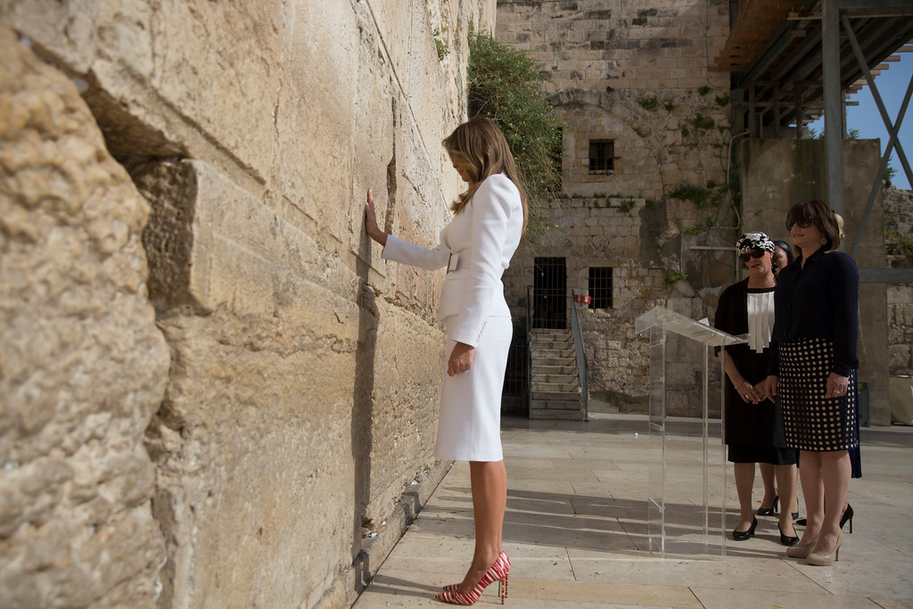 . FILE - In this Monday, May 22, 2017 file photo US first lady Melania Trump touches the Western Wall, Judaism\'s holiest prayer site, in Jerusalem\'s Old City. Trump wore a steady wardrobe of mostly black during President Donald Trump\'s overseas tour, including a prim black lace dress with a matching mantilla headcover that she wore to meet Pope Francis and a dark jacket with golden detailing on the cuff and collar that she wore for her arrival in Italy, both by Milan designers Domenico Dolce and Stefano Gabbana. (Heidi Levine, pool via AP, File)