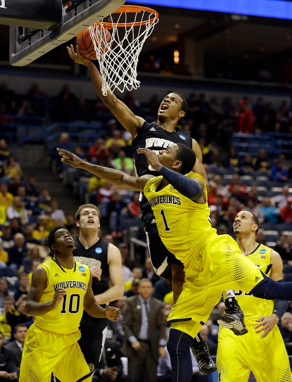 . Wofford guard Spencer Collins goes up for a shot against Michigan forward Glenn Robinson III (1) during the first half of a second round NCAA college basketball tournament game Thursday, March 20, 2014, in Milwaukee. (AP Photo/Jeffrey Phelps)
