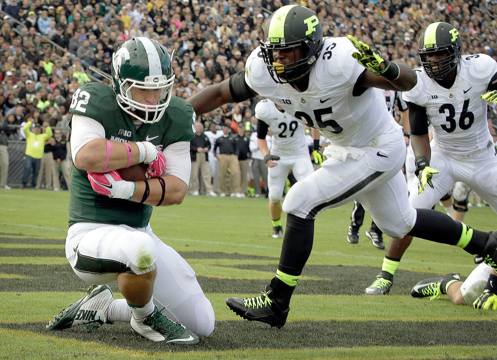 . Michigan State tight end Josiah Price (82) scores a touchdown in front of Purdue linebacker Ja\'Whan Bentley (35) during the second quarter of an NCAA college football game in West Lafayette, Ind., Saturday, Oct. 11, 2014. (AP Photo/AJ Mast)