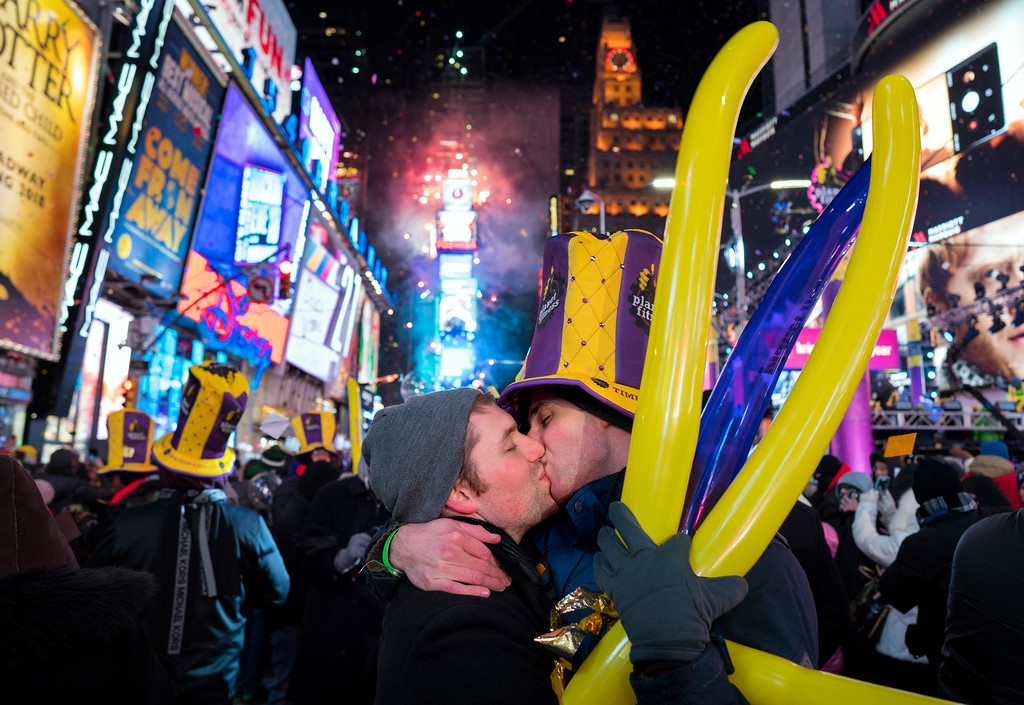 . Justin Kelly, of New York, left, kisses Patrick Graver of New York, on Times Square in New York, Monday, Jan. 1, 2018, as they take part in a New Year\'s celebration. (AP Photo/Craig Ruttle)