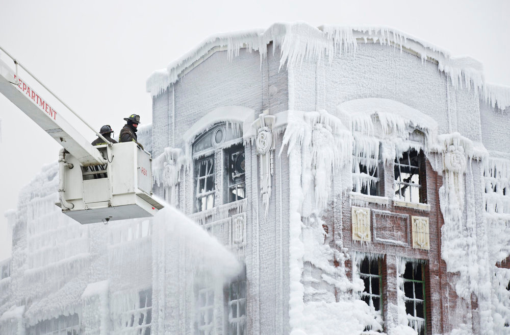 . Firefighters spray down hot spots on an ice covered warehouse that caught fire Tuesday night in Chicago January 23, 2013. Fire department officials said it is the biggest fire the department has had to battle in years and one-third of all Chicago firefighters were on the scene at one point or another trying to put out the flames. An Arctic blast continues to gripped the U.S. Midwest and Northeast Wednesday, with at least three deaths linked to the frigid weather, and fierce winds made some locations feel as cold as 50 degrees below zero Fahrenheit. (minus 46 degrees Celsius) REUTERS/John Gress