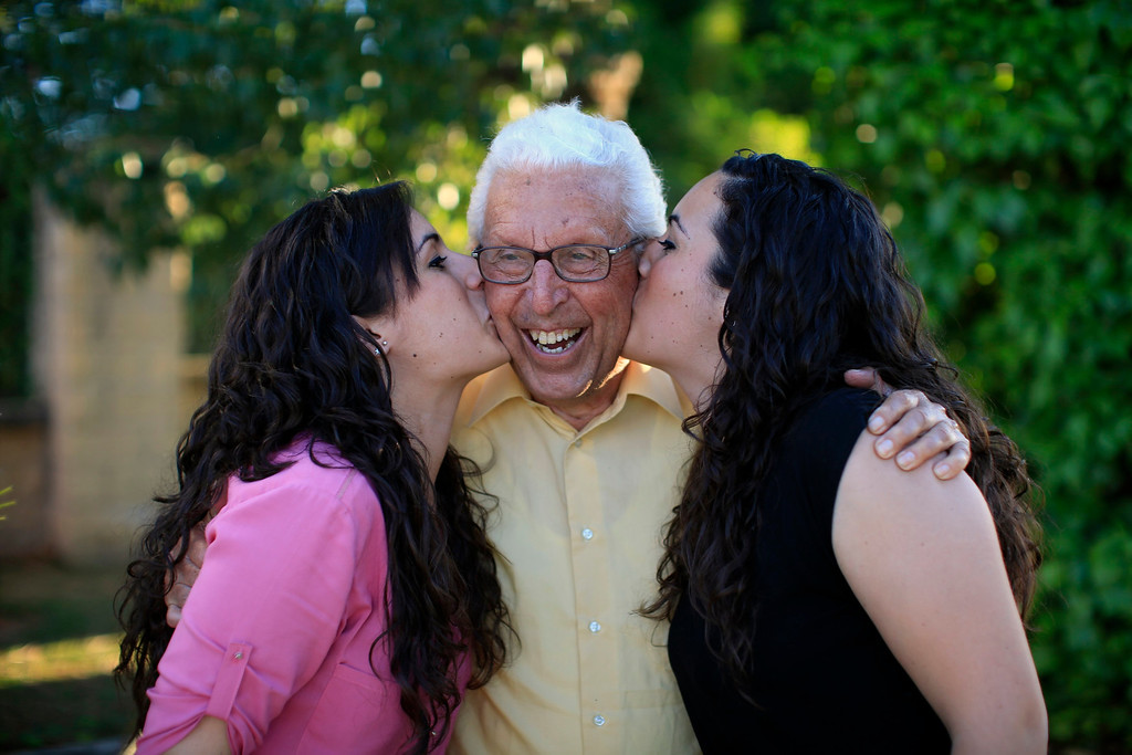 . Spanish nurses Maria Jose Marin (L), 23, and her twin sister Maria Teresa kiss their father Jose Manuel, 79, in Paradas, southern Spain June 1, 2013. After months of studying Dutch, a group of young Spanish nurses moved to the Netherlands to take up work, fleeing a dismal job market at home. Spain\'s population dropped last year for the first time on record as young professionals and immigrants who moved here during a construction boom head for greener pastures. Spain\'s jobless rate is 27 percent, and more than half of young workers are unemployed. For Spanish nurses, the Netherlands\' nursing deficit is a boon. Picture taken June 1, 2013.  REUTERS/Marcelo del Pozo