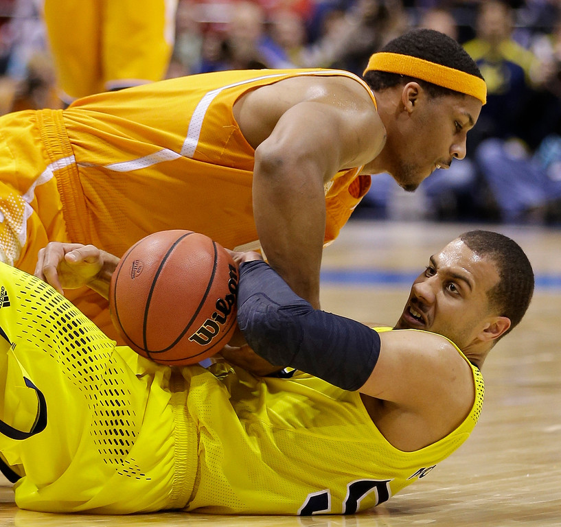 . Michigan\'s Jordan Morgan, bottom, and Tennessee\'s Jarnell Stokes go after a loose ball during the first half of an NCAA Midwest Regional semifinal college basketball tournament game Friday, March 28, 2014, in Indianapolis. (AP Photo/David J. Phillip)