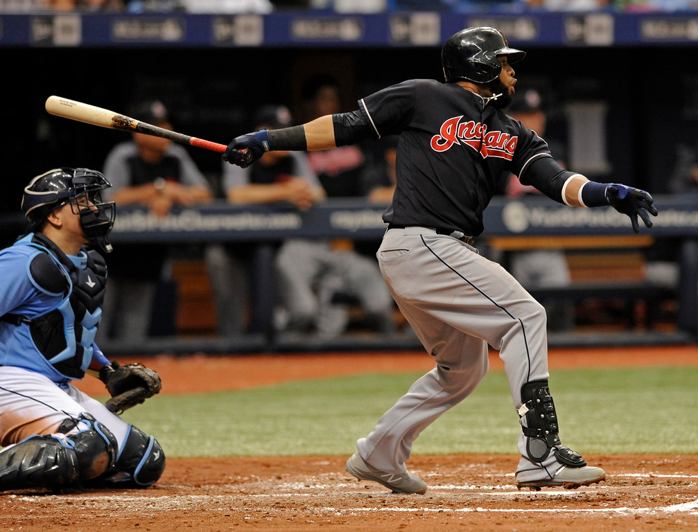 . Tampa Bay Rays catcher Jesus Sucre, left, looks on as Cleveland Indians\' Carlos Santana hits a RBI-double off starter Austin Pruitt during the fourth inning of a baseball game, Sunday, Aug. 13, 2017, in St. Petersburg, Fla. (AP Photo/Steve Nesius)