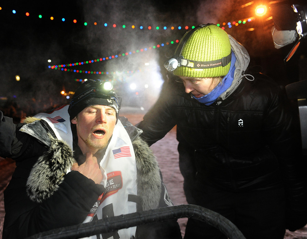 . Dallas Seavey, left, reacts after finishing the 2014 Iditarod Trail Sled Dog Race in Nome, Alaska, Tuesday, March 11, 2014. Seavey ran a blistering pace to rally from third place and win his second Iditarod in a record-breaking finish, after a sudden storm blew the front-runner out of the competition and kept another musher minutes away from her first win.  (AP Photo/The Anchorage Daily News, Bob Hallinen)